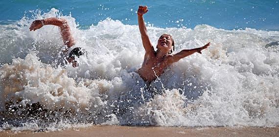 Kinderen genieten van de golven op zandstranden in Ligurië