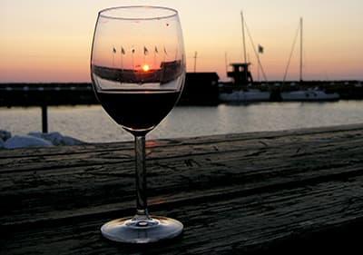 Rode wijn naast een haven tijdens de avond in Ligurië