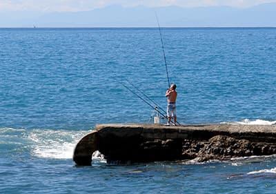 Een man is de visserij op de stenen in Recco