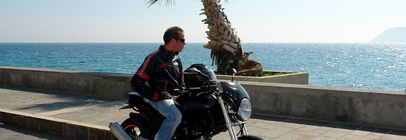 Een man met een motorfiets kijkt over de zee in Ligurië