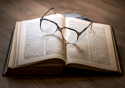 Een boek met een bril op de top