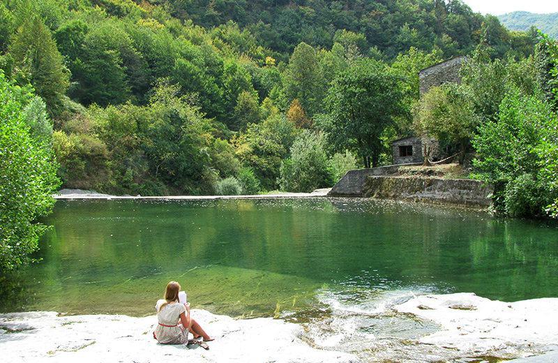 Een meisje dat een boek aan het meer van Molini di Triora