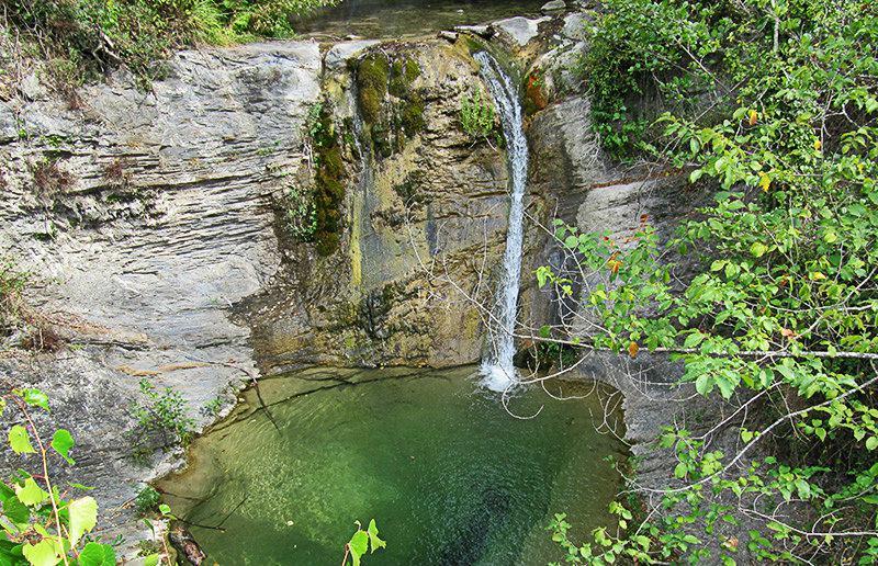Een meer met een waterval in Molini di Triora
