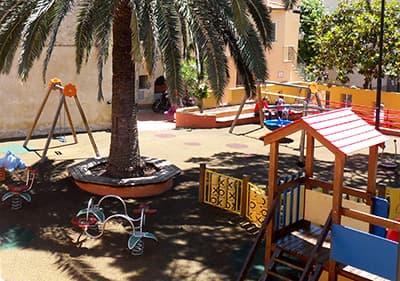Kleurrijke speelplaats in Ligurië onder de palmbomen