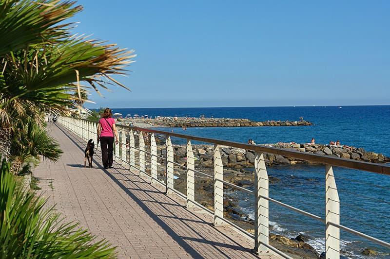Een vrouw loopt langs de kust in Riva Ligure