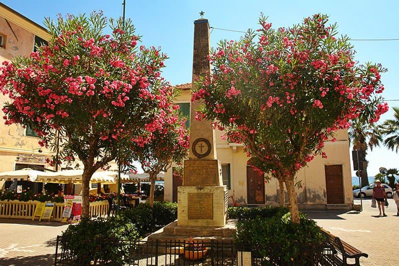 Een oude sculptuur en bloemen in Riva Ligure
