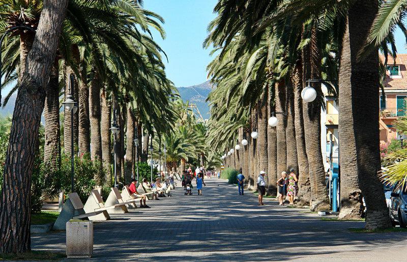 Een straat met palmbomen in Pietra Ligure