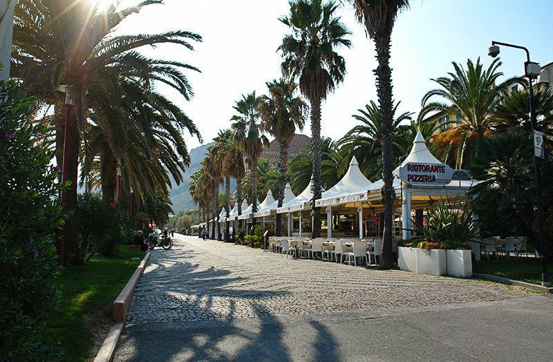 Een straat met palmbomen in Finale Ligure